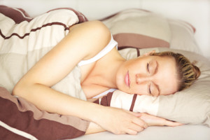 Beautiful blonde woman sleeping peacefully in her bed under her brown patterned duvet with a calm serene expression