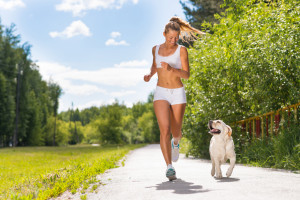 young athletic woman running on the road with white labrador, exercise outdoors